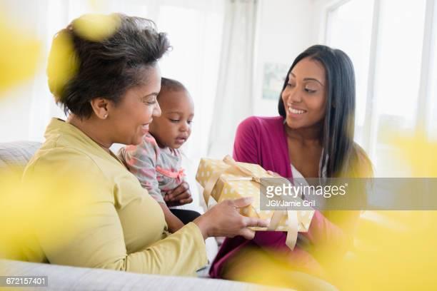 Black multi-generation family exchanging gift