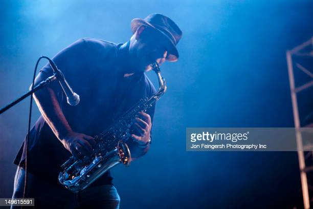 black musician playing saxophone on stage - jazz stock pictures, royalty-free photos & images