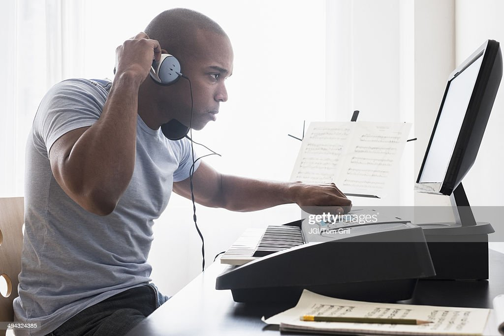 Black musician writing music with computer : Stock Photo