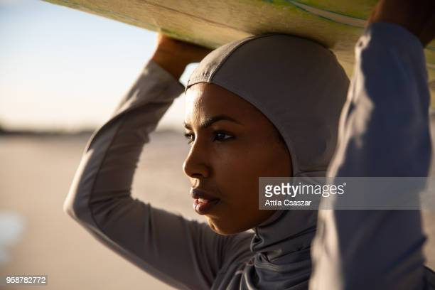 Black muslim girl wearing hijab and looking at distance while holding a surfboard