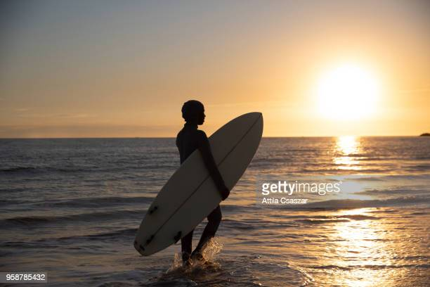 Black muslim girl wearing hijab and walking in the ocean while holding a surfboard