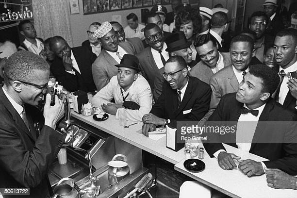 Black Muslim leader Malcolm X behind soda fountain training his camera on tux-clad Cassius Clay sitting at counter surrounded by jubilant fans after...
