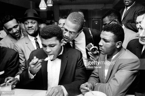 Black Muslim leader Malcolm X standing behind tuxclad Cassius Clay who is surrounded by jubilant fans after he beat Sonny Liston for the heavyweight...