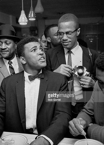 Black Muslim leader Malcolm X teasingly leaning on shoulder of tuxclad Cassius Clay who is sitting smugly at soda fountain counter surrounded by...