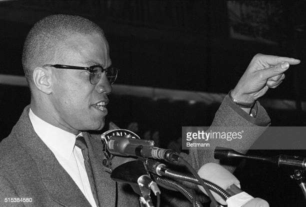 Black Muslim minister Malcolm X has assistant hold picture of fallen black men as he addresses a Harlem rally in support of integration efforts in...