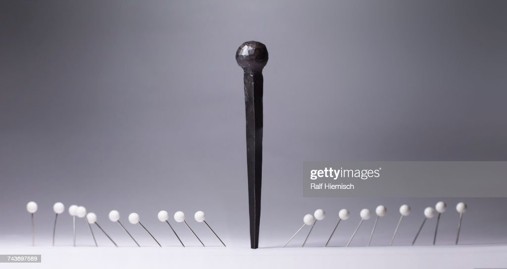 Black nail amidst white thumbtacks against gray background : Stock Photo