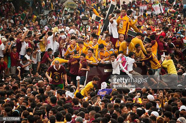 Black Nazarene devotees clamber on top of one another to to touch the cross during the Feast of Black Nazarene on January 9 2015 in Manila...