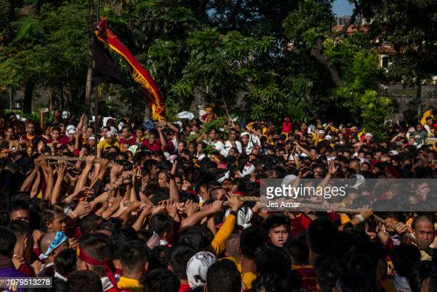 Black Nazarene devotees fight to take hold and pull on the Black Nazarenes rope on January 9 2019 in Manila Philippines The Black Nazarene is a dark...