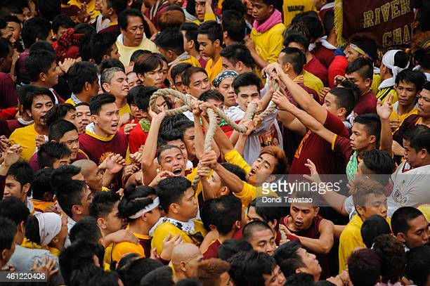 Black Nazarene devotees jostle with one another to hold the rope that pulls the Black Nazarene carriage during the Feast of Black Nazarene on January...