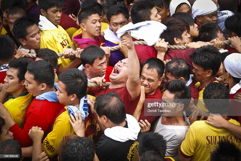 Black Nazarene devotees jostle with one another to touch the rope attached to - and pulling - the Black Nazarene, during the 406th feast of The Black Nazarene on January 9, 2013 in Manila, Philippines. Devotees march barefoot as a sign of sacrifice during the procession as the Black Nazarene is carried in turn through Manila's thouroughfares. The dark wood sculpture of Jesus was brought to the Philippines in the 1600s during the Spanish colonization of the Philippines and is revered by Catholic devotees who claim the statue possess miraculous powers.