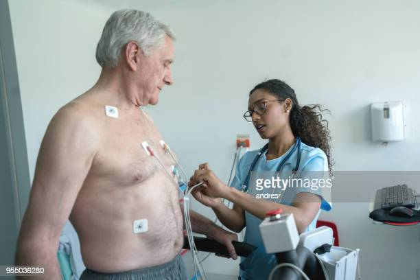 Black nurse putting electrones on a senior patient who is ready for a stress test on a treadmill