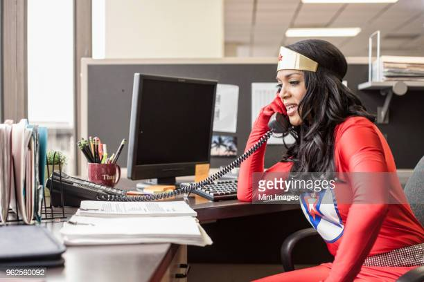 A black office superhero businesswoman takes a call in her office from a client.