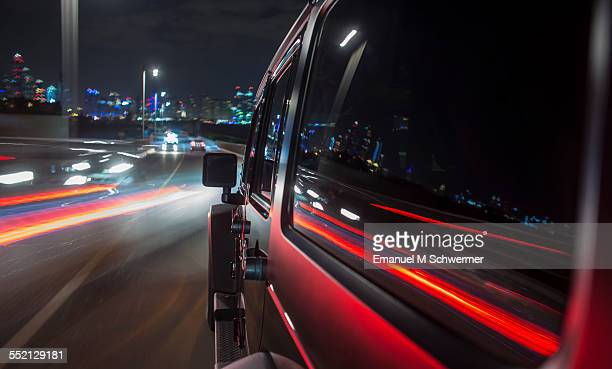 black off-road car drives in a city during night