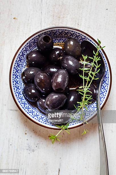 Black olives in bowl with thyme