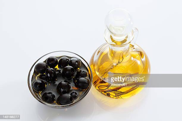Black olives in glass bowl and bottle of olive oil on white background