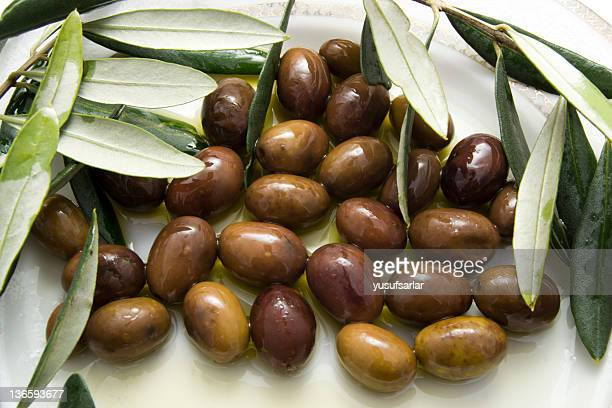 black olives in olive oil - kalamata olive stock photos and pictures