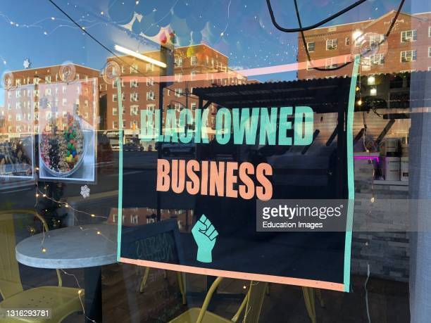 Black Owned Business sign in local storefront window, MisFits Nutrition, Queens, New York.