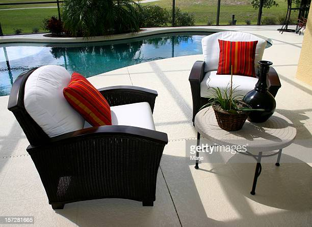 Black, padded patio chairs with red pillows by a pool