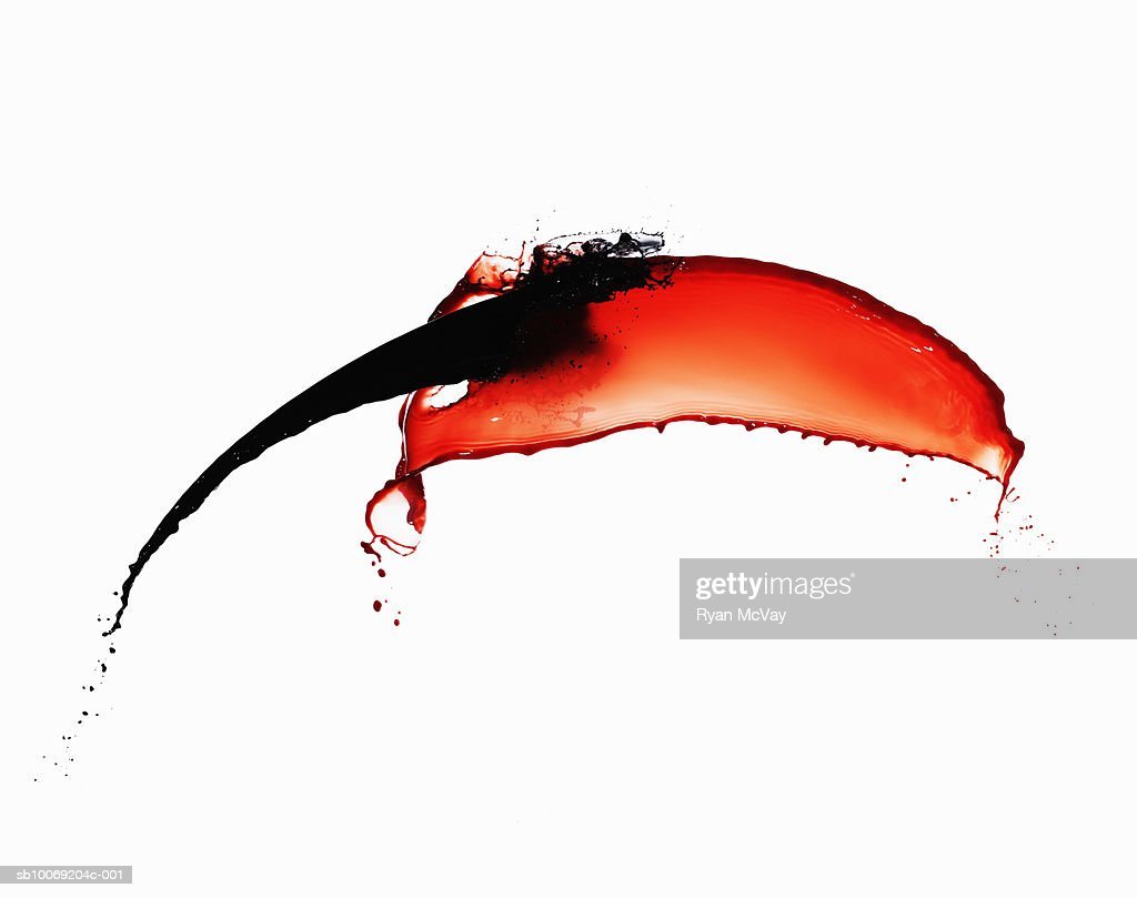 Black paint and red paint against white background, close-up : Stockfoto