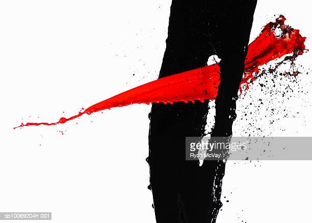 Black paint and red paint against white background, close-up