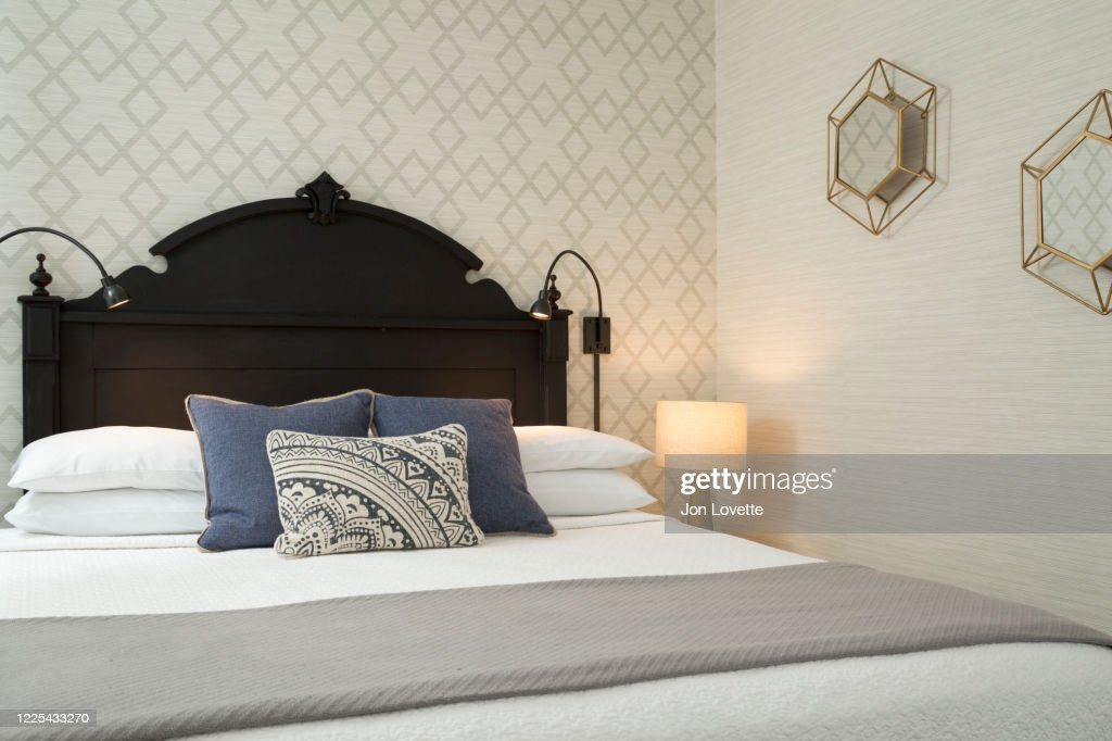 Black Painted Headboard With Beige Painted And Wallpapered Walls High Res Stock Photo Getty Images