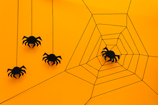Black paper spider with web on yellow background. Halloween concept. Paper cut style. Top view 1034849662