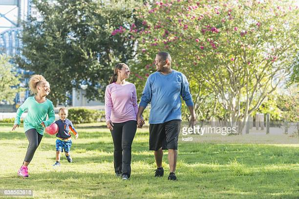Black parents walking in park, children running, playing