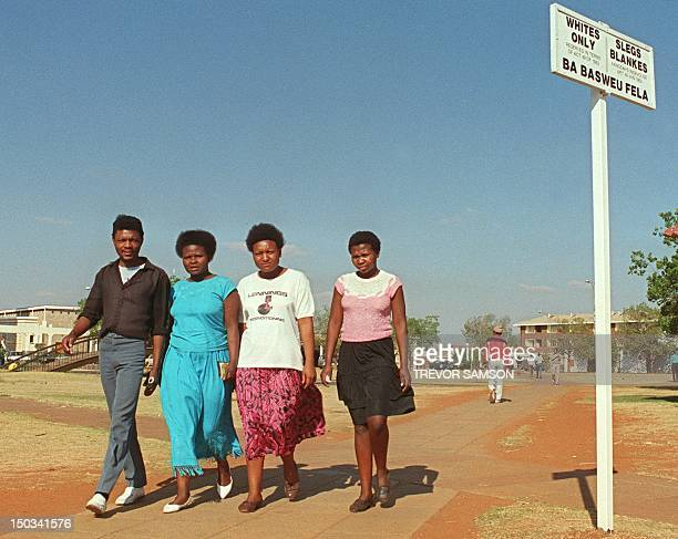 Black people pass a segregation sign setting aside seperate areas for blacks and whites 01 September1989 in the town of Carltonville