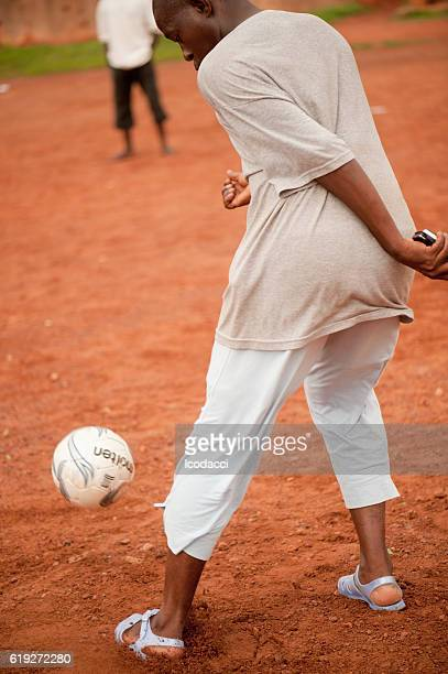 Black people playing soccer in a rural village