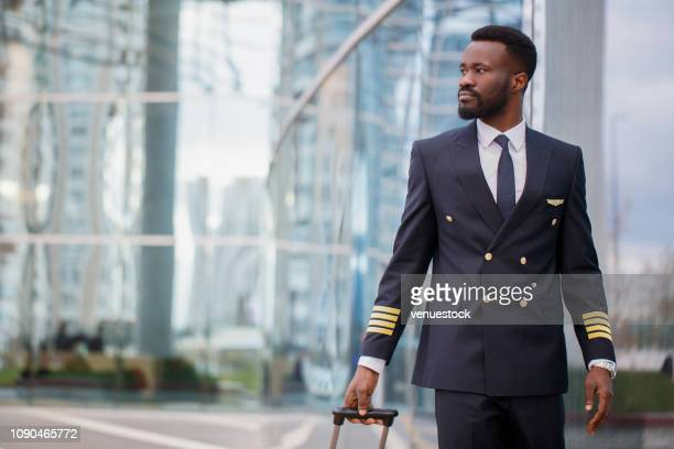black person pilot walking at the airport - piloting stock pictures, royalty-free photos & images