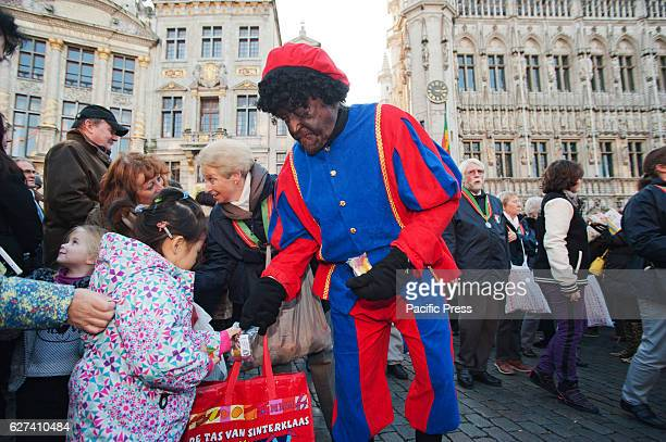 Black Pete traditionally the helper of SaintNicholas gives candy to the children on the annual parade of SaintNicholas through Brussels