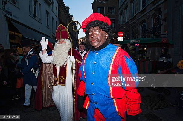 Black Pete who is traditionally depicted as the helper of SaintNicholas walks in front on the annual parade of SaintNicholas through Brussels