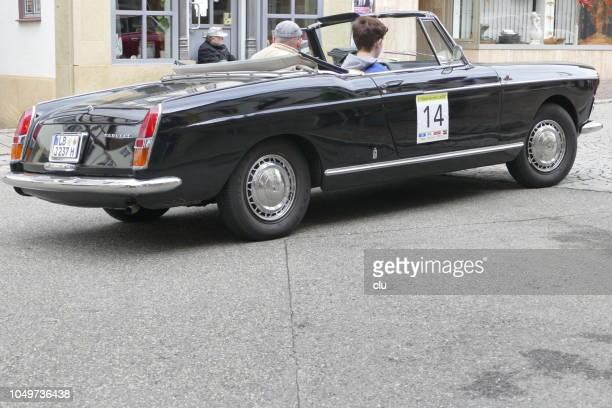Noir Peugeot Cabrio 404 sur une route pavée