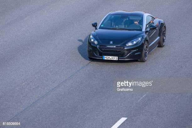 Black Peugeot RCZ sportscar driving on a german highway
