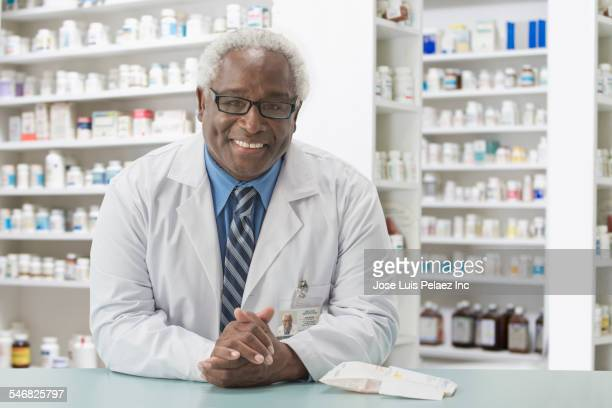 Black pharmacist smiling behind counter