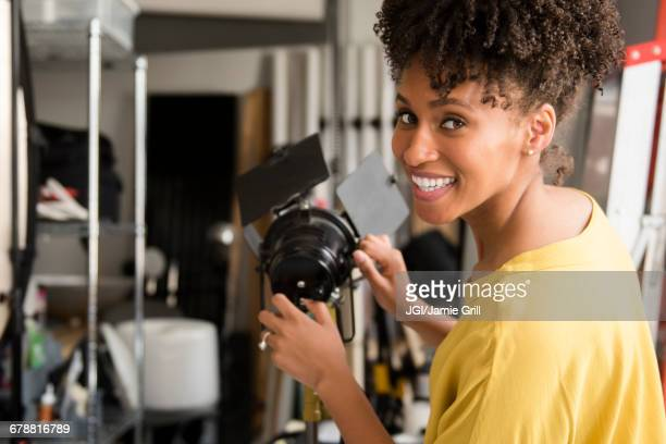 black photographer adjusting lamp in studio - behind the scenes stock pictures, royalty-free photos & images