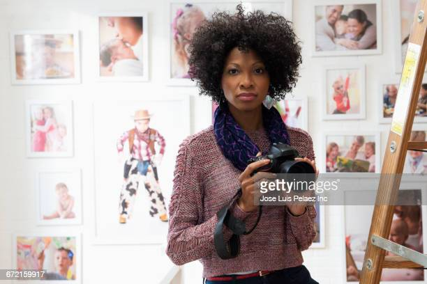 black photographer holding camera in studio - photographer stock pictures, royalty-free photos & images