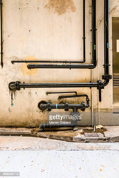 Black pipes on wall in alleyway