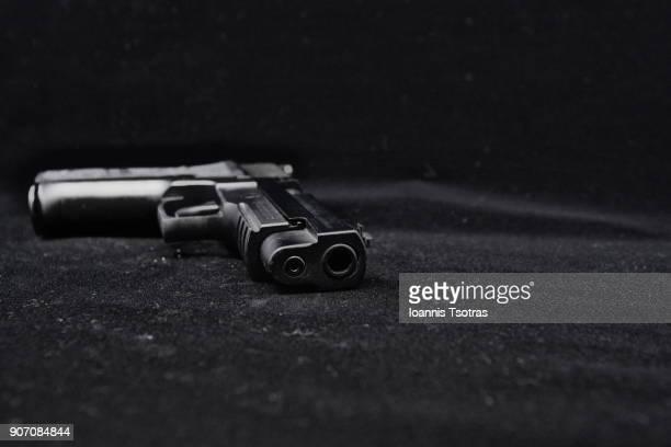 a black pistol  (gun) - arma fotografías e imágenes de stock