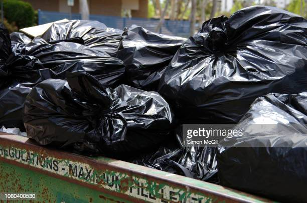 black plastic garbage bags in an industrial skip bin - garbage bin stock pictures, royalty-free photos & images