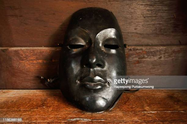 black plastic mask on wooden background - black mask disguise stock pictures, royalty-free photos & images