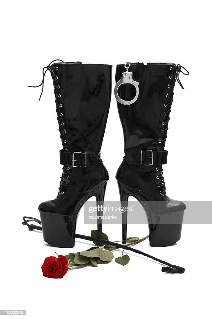 Schwarze Plateau-Stiefel mit Peitsche und rose : Stock-Foto