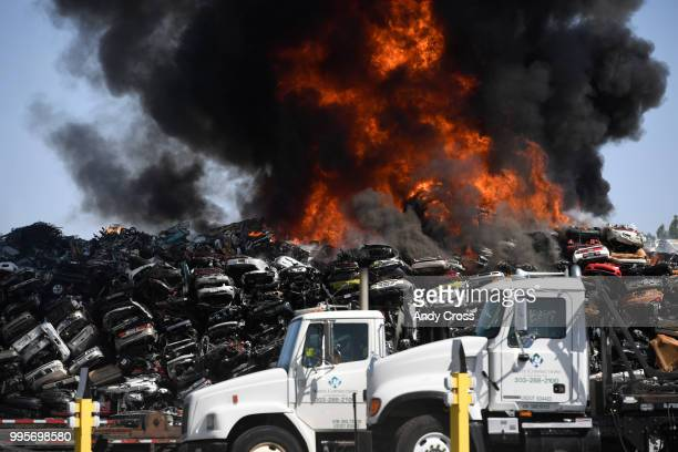 A black plume of smoke engulfs a large pile of crushed vehicles near 5600 York St July 10 2018