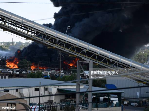 Black plume of smoke rises from a fire in a large pile of crushed vehicles near 5600 York St July 10 2018