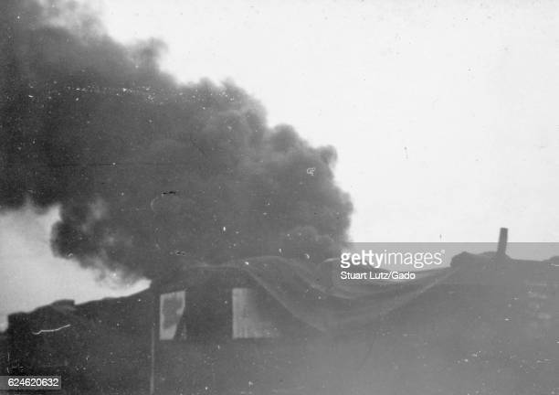 A black plume of smoke rising from an unseen fire a structure that has been built in to the earth is seen covered with a large tarp in the foreground...