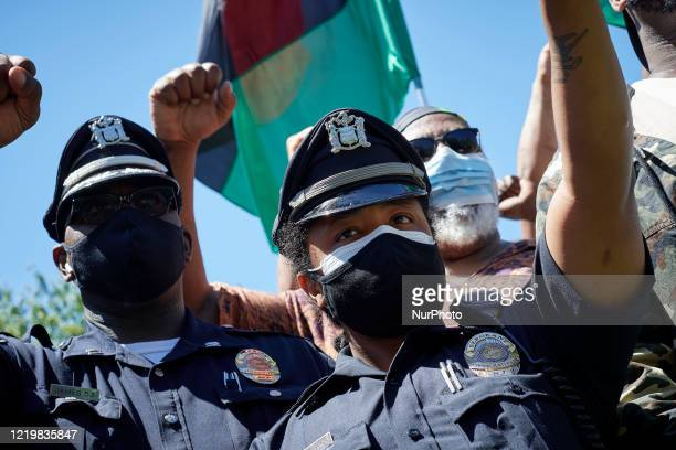 Black police officers with the Camden County Police Department join community activist during a rally hosted by Black Men Rising at the base of were...