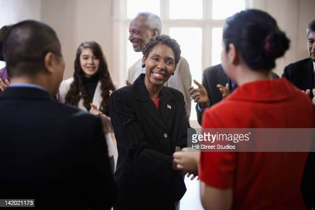 black politician shaking hands with supporters - politician stock pictures, royalty-free photos & images