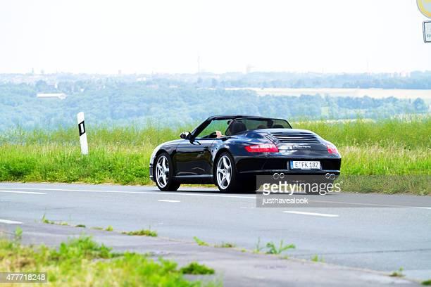 Black Porsche Carrera driving into valley Ruhr