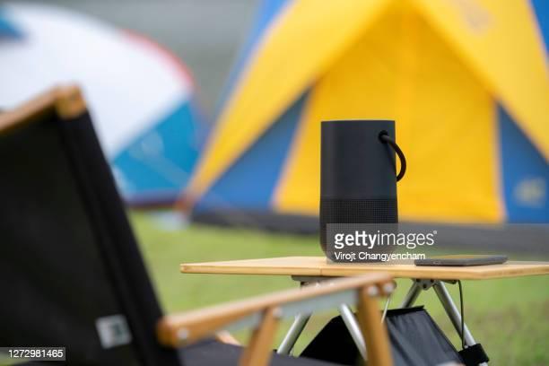 black portable speaker on the outdoor table - ブルートゥース ストックフォトと画像