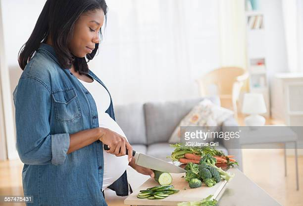 Black pregnant woman chopping vegetables in kitchen